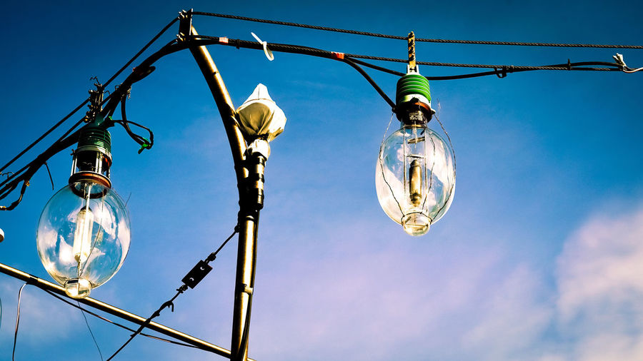 Low angle view of illuminated light bulbs against sky