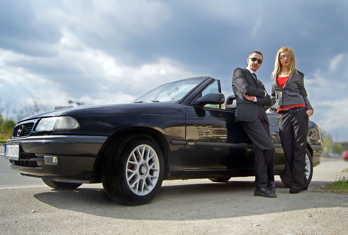 Business couple posing for camera by convertible car Blonde Suit Black Car Businessman Businesswoman Cabriolet Car Convertible Day Girl Outdoors Sunglasses Two People Vehicle Well-dressed Young Women