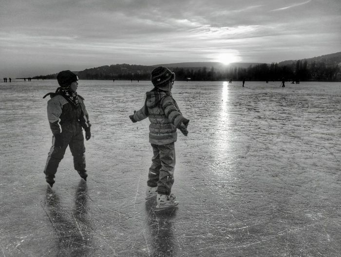 Siblings ice-skating on rink against sky during sunset