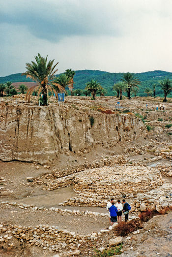 """The 6,000 year old ruins of Megiddo (Armageddon), built by King Soloman - Israel ............According to the Book of Revelation in the New Testament of the Bible, Armageddon (/ˌɑːrməˈɡɛdən/, from Ancient Greek: Ἁρμαγεδών Harmagedōn, Late Latin: Armagedōn, from Hebrew: הר מגידו Har Megiddo) is the prophesied location of a gathering of armies for a battle during the end times, variously interpreted as either a literal or a symbolic location. The term is also used in a generic sense to refer to any end of the world scenario. """"Mount"""" Tel Megiddo is not actually a mountain, but a tell (a hill created by many generations of people living and rebuilding on the same spot) on which ancient forts were built to guard the Via Maris, an ancient trade route linking Egypt with the northern empires of Syria, Anatolia and Mesopotamia. Megiddo was the location of various ancient battles, including one in the 15th century BC and one in 609 BC. Modern Megiddo is a town approximately 25 miles (40 km) west-southwest of the southern tip of the Sea of Galilee in the Kishon River area in Israel. People Nature Real People Men Sky Landscape Tree Day Outdoors Sand Mountain Palm Tree Armageddon Togetherness Scenics Beauty In Nature Two People Megiddo"""