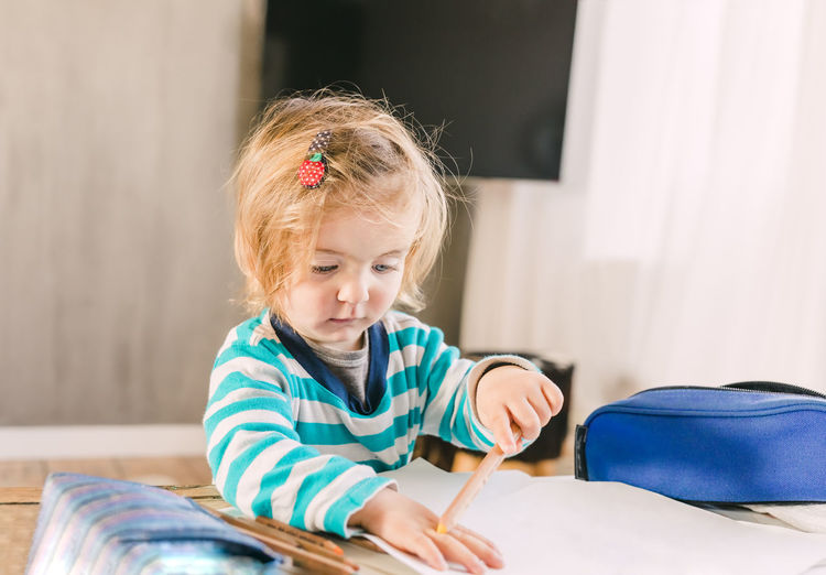 Toddler girl painting around her hand - Hindeloopen, Netherlands Toddler  Toddlerlife Painting Holding Learning Education Paper Coloring Crayon Portrait Headshot Head And Shoulders Human Hand Shape Table Challenge Effort Concentration Serious Looking Down Hair Clip Striped Sweater Living Room Caucasian Child Childhood Blond Hair Hair Indoors  One Person Girls Lifestyles Women Females Real People Front View Home Interior Sitting Innocence Hairstyle