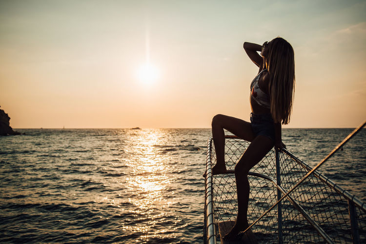 Water Sea Sky Sunset One Person Real People Beauty In Nature Scenics - Nature Horizon Horizon Over Water Lifestyles Leisure Activity Sitting Sun Women Nature Tranquility Adult Tranquil Scene Outdoors Looking At View Hairstyle