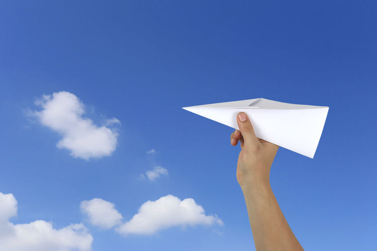 Cropped hand holding paper airplane against blue sky