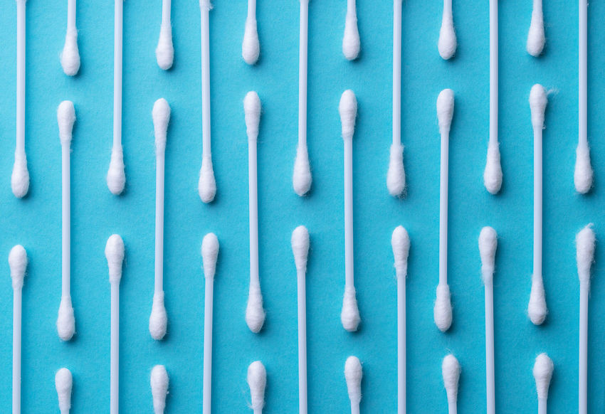 Multiple ear sticks over blue background Hygiene In A Row Blue Close-up Colored Background Cosmetic Ear Stick Large Group Of Objects Macro Object Organized Overhead View Pattern Stick Studio Shot Swab Wax White