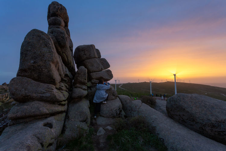 Rear view of statue by rock against sky during sunset