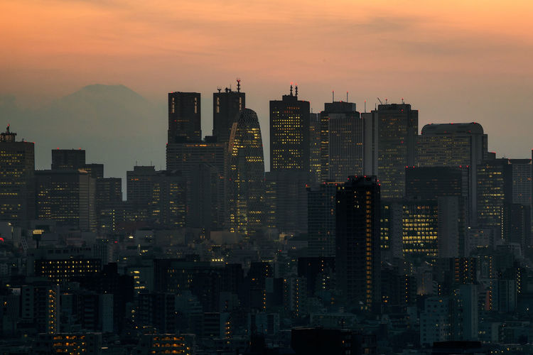 View of skyscrapers in city at sunset