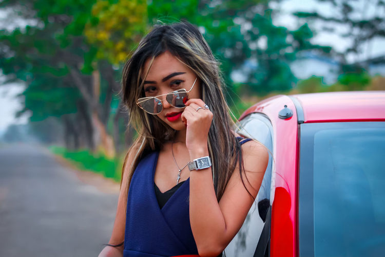 Portrait of beautiful young woman wearing sunglasses by car