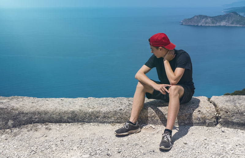 Full length of man sitting on rock by sea