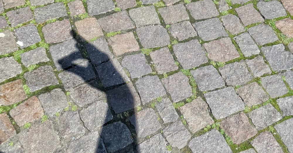 Shadow of cropped hand gesturing on footpath during sunny day