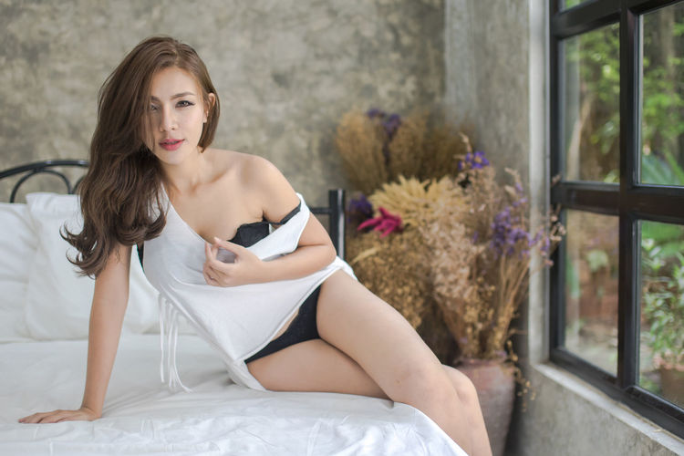 Sensuous woman sitting on bed at home