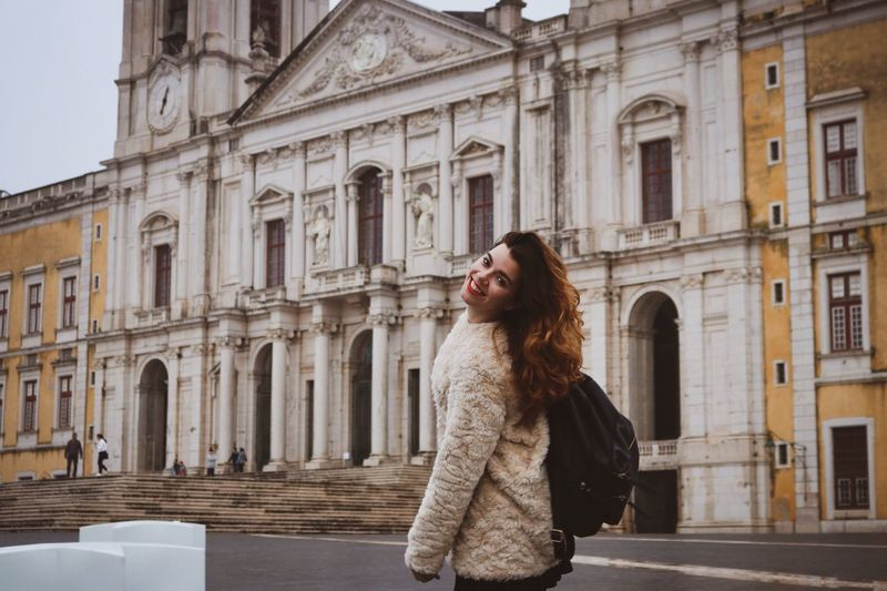 Portrait of young woman standing against built structure in city