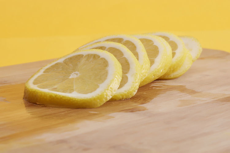 Sliced lemon at cutting board isolated on color background Food And Drink Food Healthy Eating Fruit Wellbeing Table Freshness Indoors  Close-up Wood - Material Still Life Yellow SLICE No People Cutting Board Citrus Fruit Selective Focus Cross Section Halved Single Object