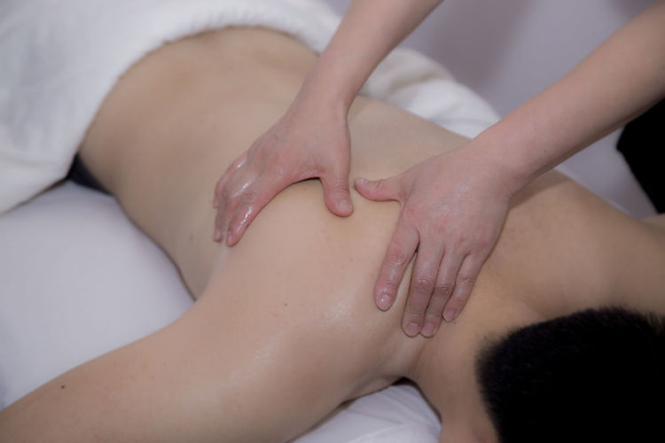 Cropped hands of woman giving massage on man at spa