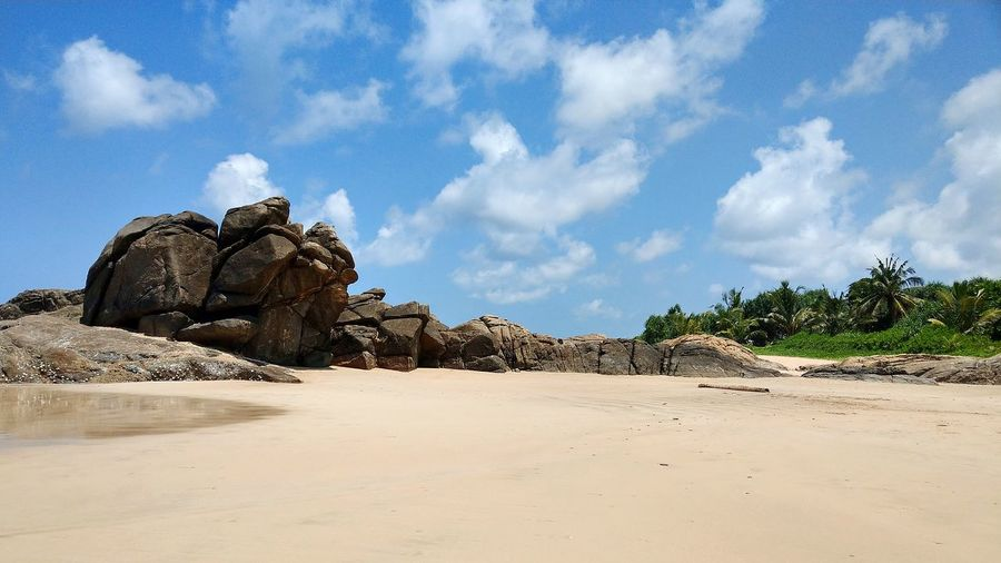 Panoramic View Of Rocks On Beach Against Sky