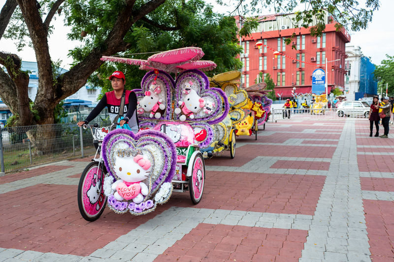 Malacca Built Structure Architecture Transportation Building Exterior City Day Incidental People Street Real People Mode Of Transportation Footpath Land Vehicle Tree Outdoors Plant Building Scooter Nature People Travel Paving Stone