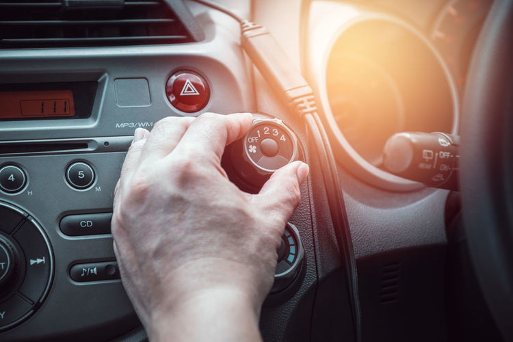 Cropped hand of man adjusting fan button in car