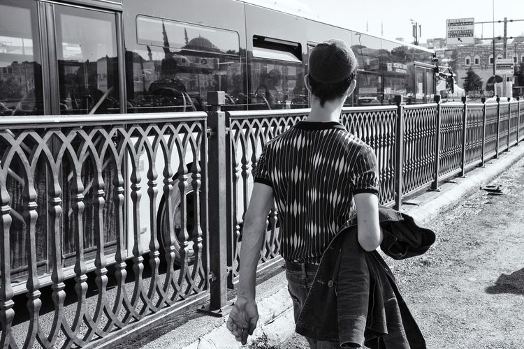 Rear view of man standing by railing in city
