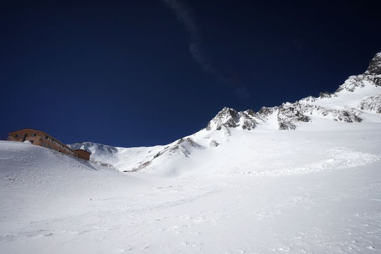Snow covered mountain against blue sky