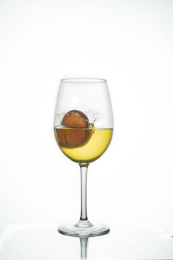 Close-up of wine in glass against white background