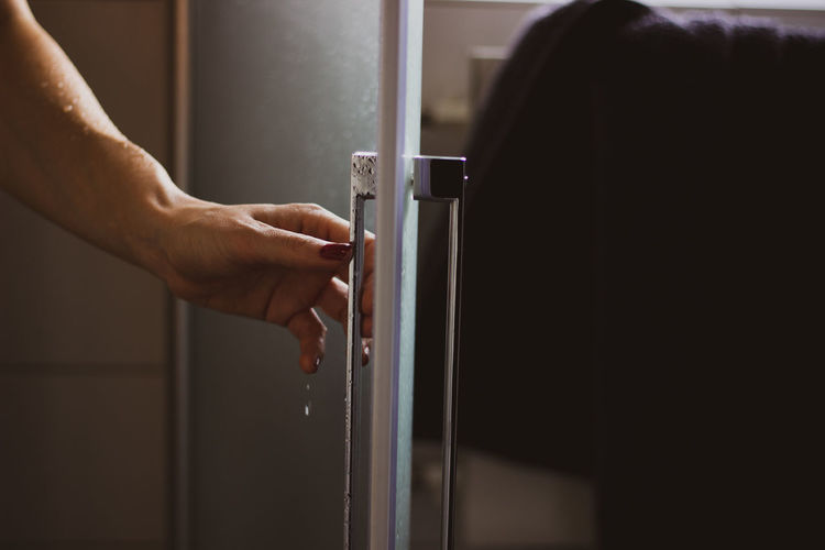 Cropped image of woman holding bathroom door after shower