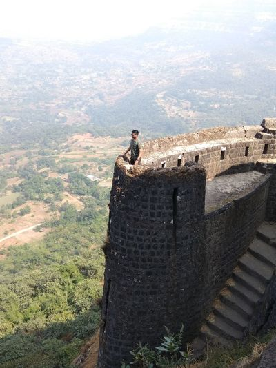 Young man standing on fort overlooking landscape