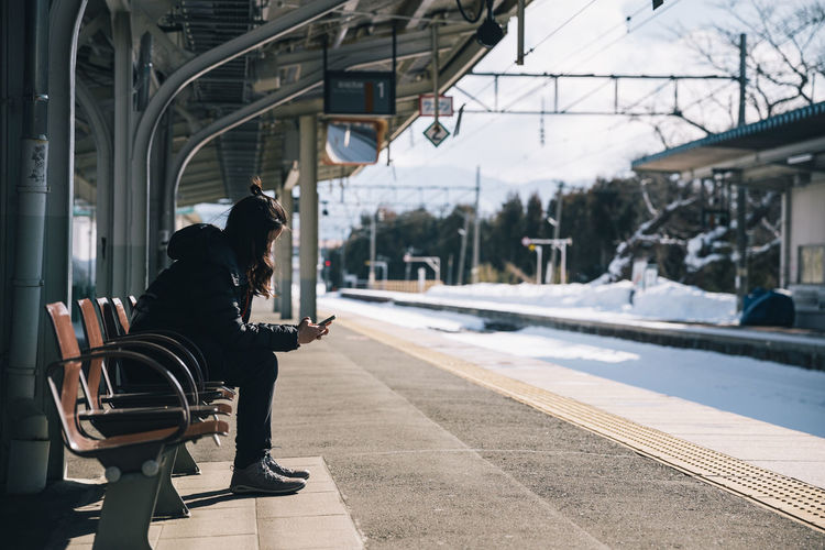 Side view of woman using smart phone sitting on bench at railroad station