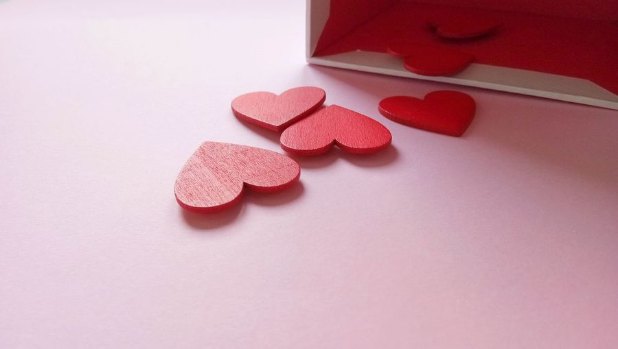 Close-up of box with red heart shapes over pink background