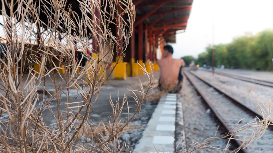 Rear view of man on railroad tracks against sky