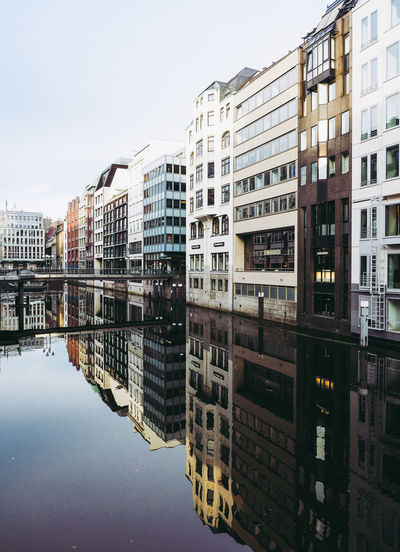 Reflection Of Buildings On River Against Sky