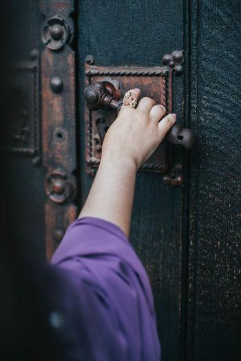 Close-up of human hand on metal door