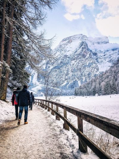 Rear view of men walking on footpath towards snowcapped mountain