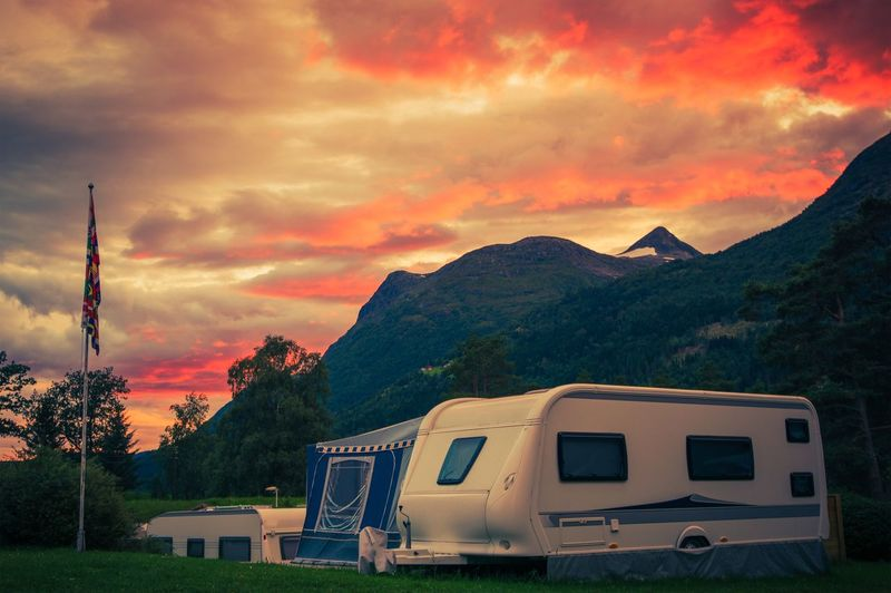 Scenic Camping Sunset. Sunset Sky Over Campground with Travel Trailers. Campsite Caravan Camping. Camping Campsite Norway Beauty In Nature Car Cloud - Sky Land Vehicle Mode Of Transportation Motor Vehicle Mountain Mountain Range Nature No People Norwegian Orange Color Outdoors Plant Scenics - Nature Sky Sunset Tranquil Scene Tranquility Transportation Travel Trailer Tree