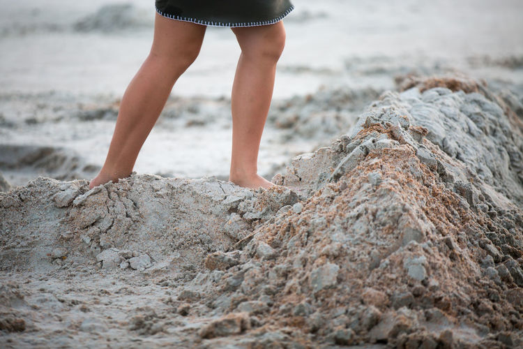 Low Section View Of Girl Standing On Sand At Beach