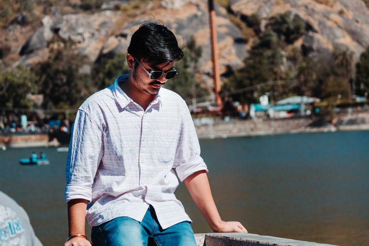 Man looking away while sitting against lake