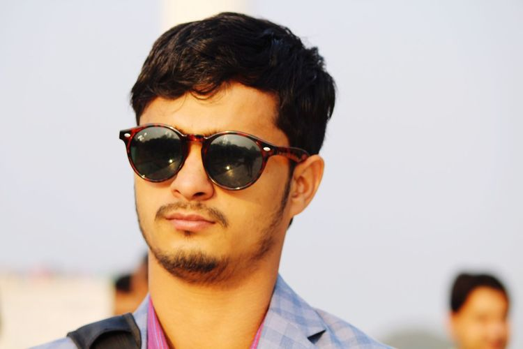 Young man wearing sunglasses against clear sky
