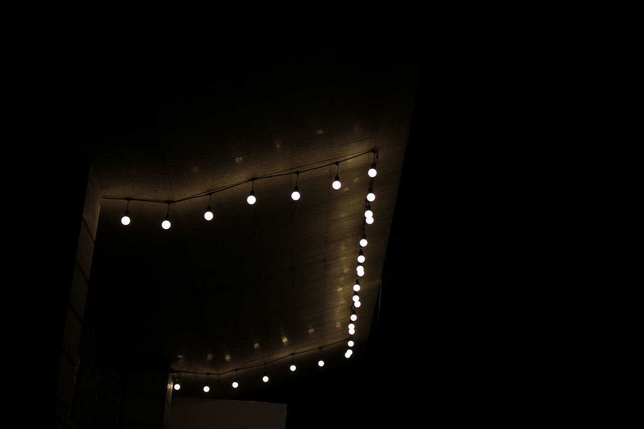 LOW ANGLE VIEW OF ILLUMINATED LIGHT BULBS AT NIGHT