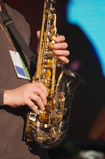 Midsection Of Man Playing Saxophone At Music Concert