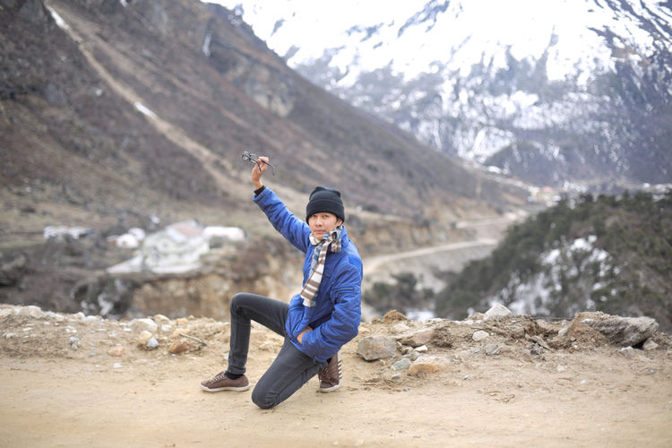 Asian man take off glasses Adults Only Adventure Beauty In Nature Cold Temperature Day Fashion Full Length Glasses Happiness Healthy Lifestyle India Landscape Mountain Mountain Range Nature One Person Outdoors People Portrait Snow Vacations Warm Clothing Winter Winter Sport Young Adult