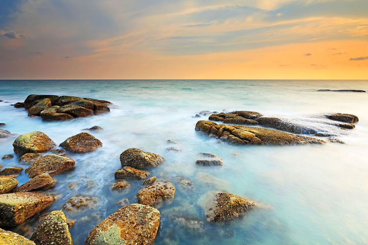 Beautiful seascape with sunset on the rocky shore of a tropical beach and Island Sea Water Horizon Over Water Sky Horizon Scenics - Nature Beauty In Nature Rock Sunset Solid Beach Motion Tranquil Scene Cloud - Sky Land Rock - Object Tranquility Nature Idyllic No People Outdoors Seascape Coastline Sunrise ASIA Thailand Island Beauty In Nature Tranquility Stone