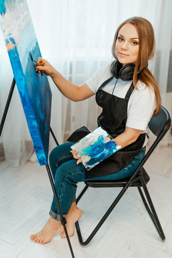 Portrait of woman painting on easel