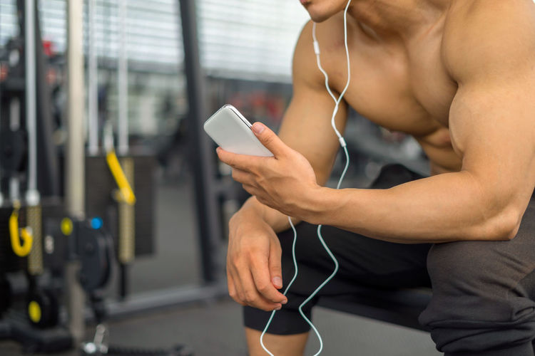 Midsection Of Shirtless Muscular Man Using Mobile Phone In Gym