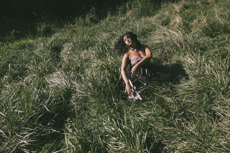 High angle view of contemplating woman tossing hair while sitting on field