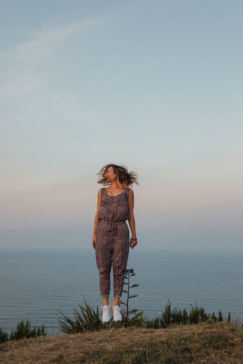Full Length Of Woman Jumping While Tossing Hair Against Sea And Sky During Sunset