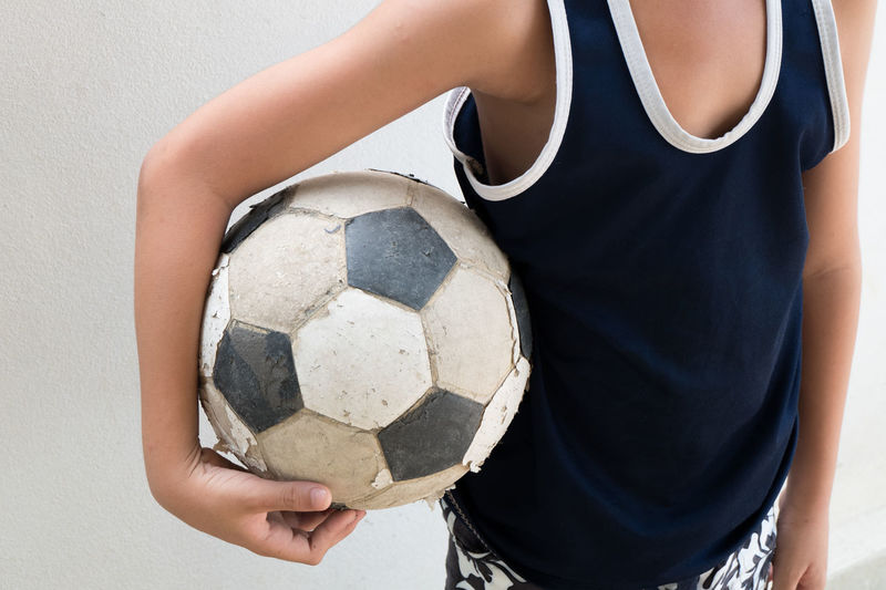 Close-Up Of Boy Holding Football Over White Background