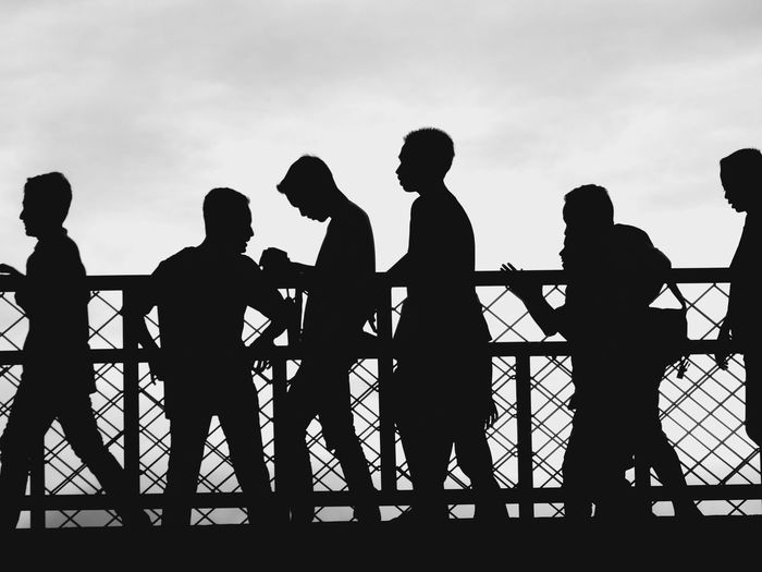 Silhouette men standing by railing against sky