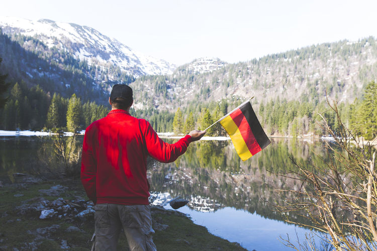 Rear view of man with flags standing against snowcapped mountains