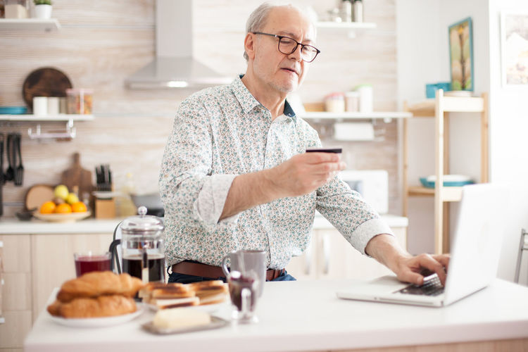 Man using laptop on table at home