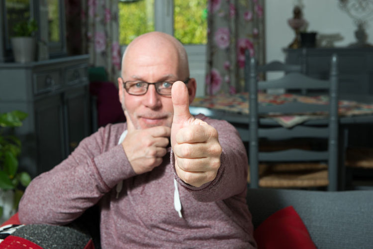 Portrait of bald mature man gesturing thumbs up on sofa at home