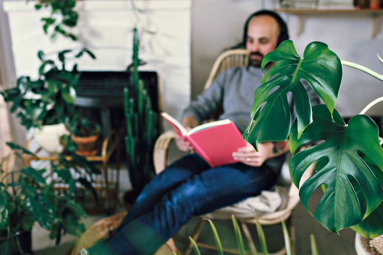 Man holding book while sitting on plant