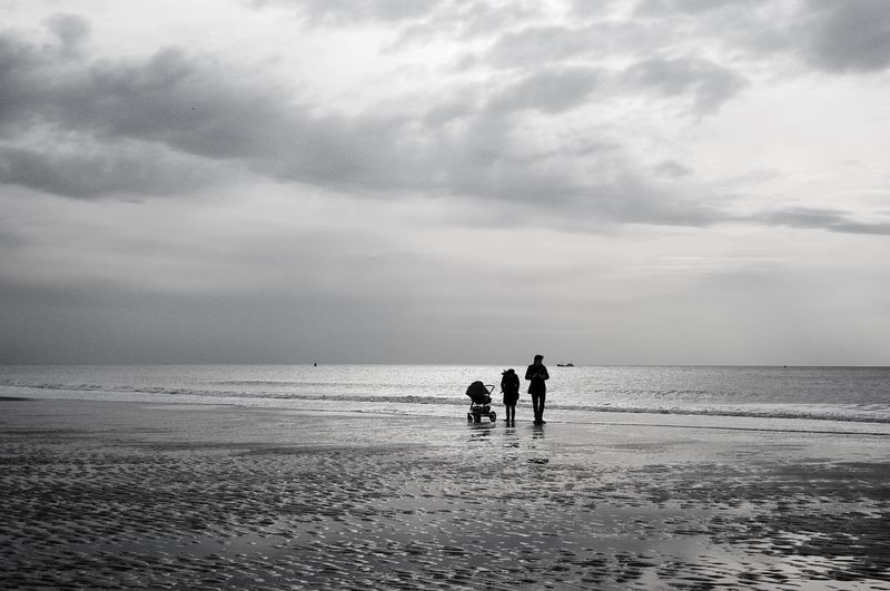 Silhouette People With Baby Carriage At Beach Against Sky